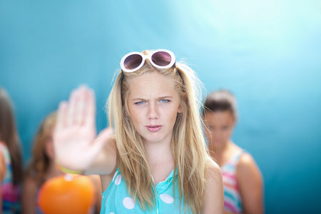 frowns: Teenage girl holding hand out to stop
