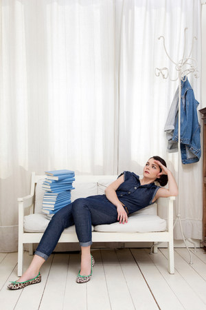 fedup: Woman reclining on seat with pile of books