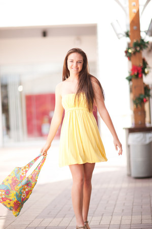 materialism: Woman carrying shopping bag in mall
