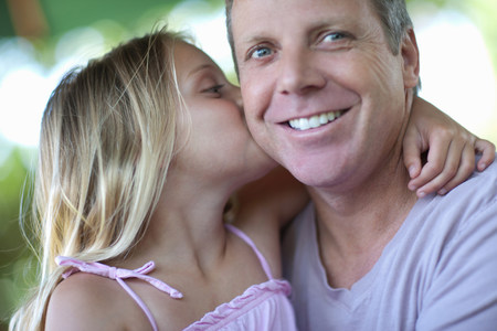 release: Girl kissing father outdoors