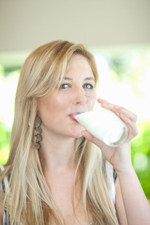 Woman drinking glass of milk outdoors LANG_EVOIMAGES