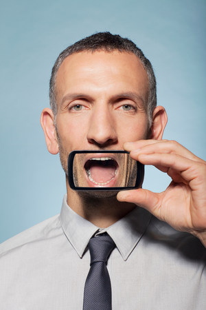 Man with smartphone over mouth
