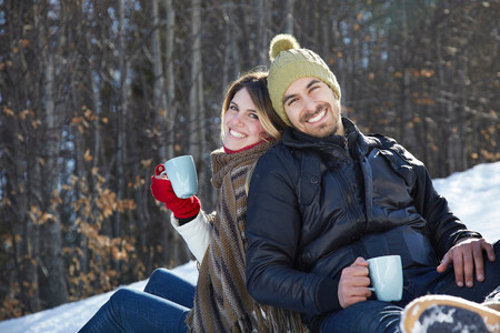 Portrait of couple sitting in snow with hot drinks LANG_EVOIMAGES