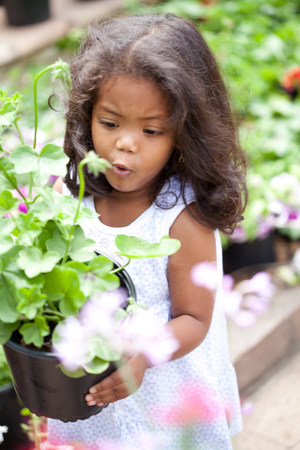 Girl carrying potted flowers outdoors LANG_EVOIMAGES