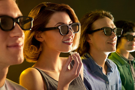 Row of people watching 3D movie,woman with popcorn LANG_EVOIMAGES