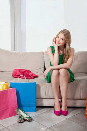 customer facing: Young woman sitting on sofa with shopping bags LANG_EVOIMAGES