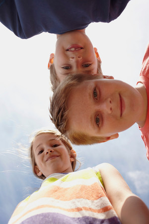 Girl and two boys looking at camera,viewed from below