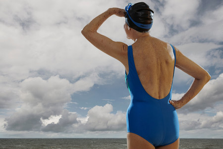 Senior woman wearing swimsuit looking towards sea,shielding eyes