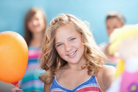 tweens: Smiling girl holding balloon