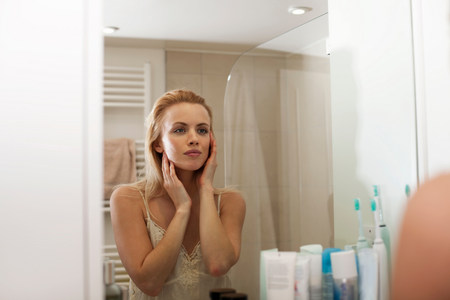narcissist: Young woman looking in bathroom mirror LANG_EVOIMAGES