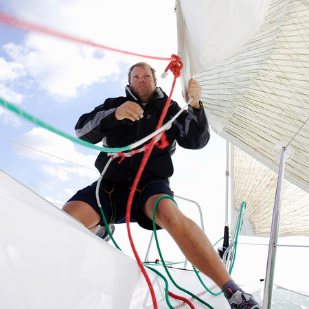 Man on yacht,pulling ropes