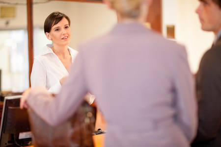 Hotel receptionist talking to guests