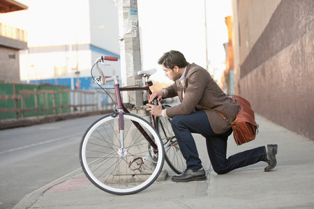 25 29 years: Man locking bicycle on city street