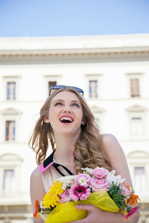 Happy young woman outdoors with bouquet of flowers