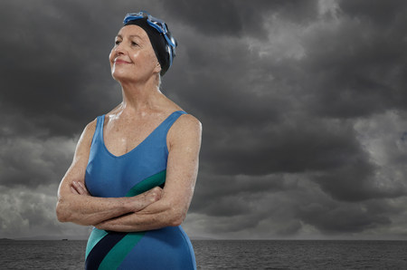 hopefulness: Senior woman wearing swimsuit with arms folded