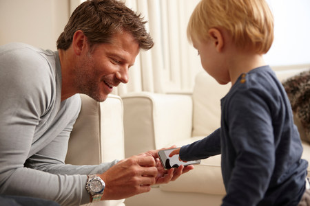 engrossed: Father holding smartphone,son using touchscreen