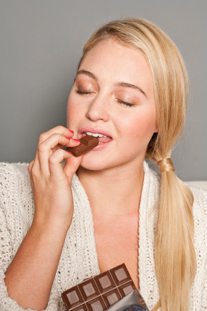 tempted: Woman biting chocolate