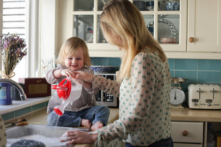 sinks: Mother washing up,daughter pouring water