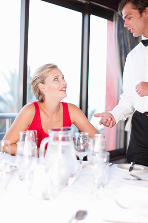 19 year old boy: Woman talking to waiter at restaurant LANG_EVOIMAGES
