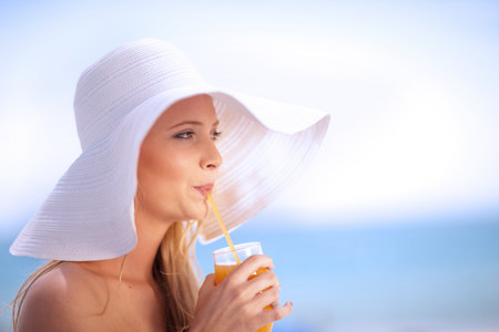 Woman in floppy hat drinking juice LANG_EVOIMAGES