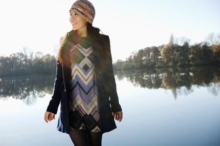 Woman walking by still lake