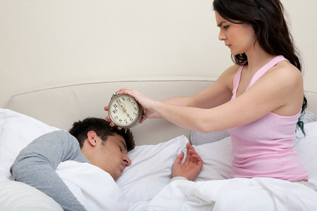 Couple in bed,woman holding alarm clock near mans head