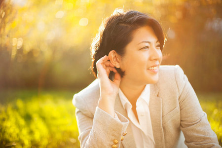 Smiling businesswoman sitting outdoors LANG_EVOIMAGES