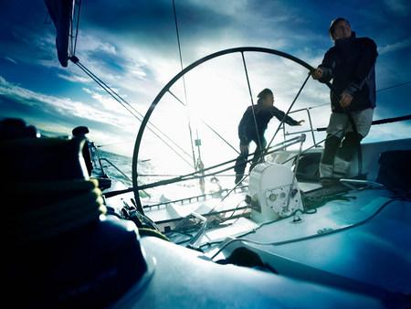 Sailors steering yacht