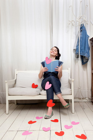 housing lot: Woman reading book with heart shapes