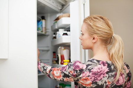 refrigerator: Young woman looking in refrigerator