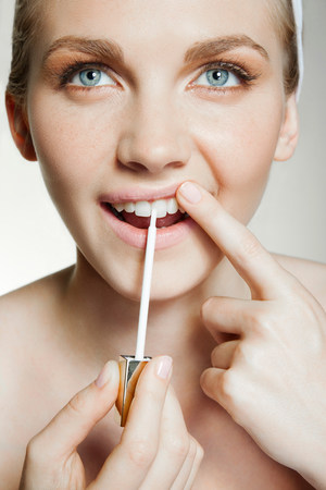 narcissist: Woman using tooth whitening brush