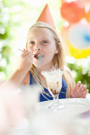 cropped out: Girl having ice cream sundae at party LANG_EVOIMAGES