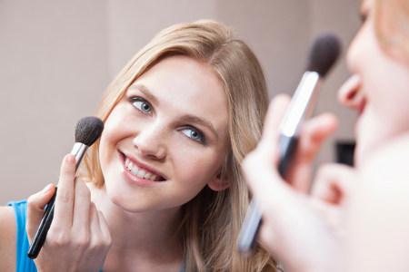 narcissist: Young woman applying blusher in the mirror