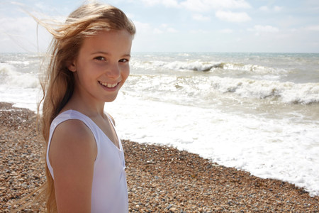 Girl on shingle beach by the sea,smiling at camera