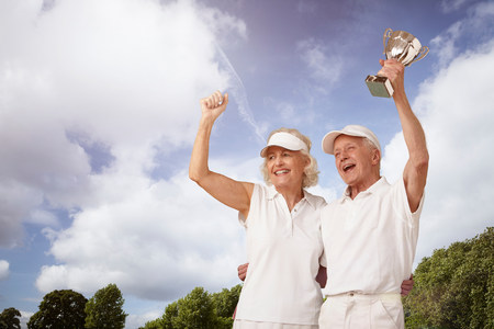 70s tennis: Senior couple holding tennis trophy and cheering