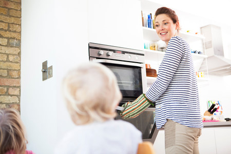 Mother wearing oven gloves opening oven