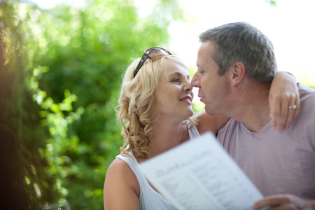 smooching: Smiling couple with menu outdoors