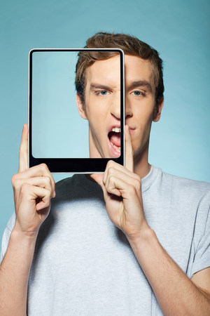 silliness: Man covering half his face with digital tablet LANG_EVOIMAGES