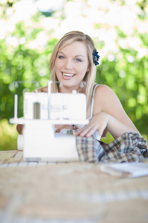 self sufficient: Woman working on sewing machine
