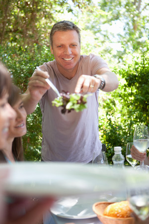 Man serving salad at table outdoors