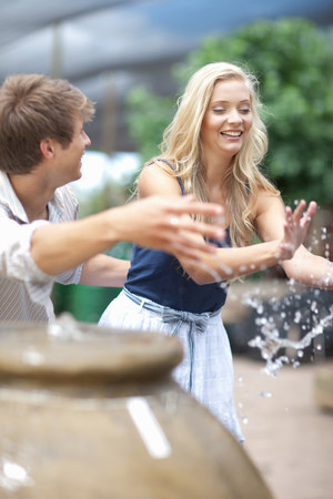 19 year old boy: Man splashing girlfriend in fountain LANG_EVOIMAGES