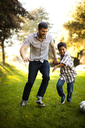 run down: Father and son playing soccer together