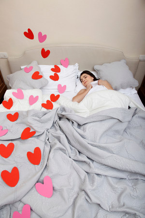 Woman asleep in bed with heart shapes on bedclothes