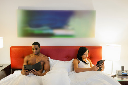 electronic organiser: Couple using e-readers in bed LANG_EVOIMAGES