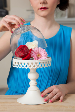 Woman lifting lid of cake stand with flowers