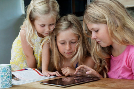 Three girls looking at digital tablet LANG_EVOIMAGES