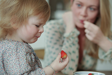 disgusted: Toddler holding strawberry,pulling face LANG_EVOIMAGES