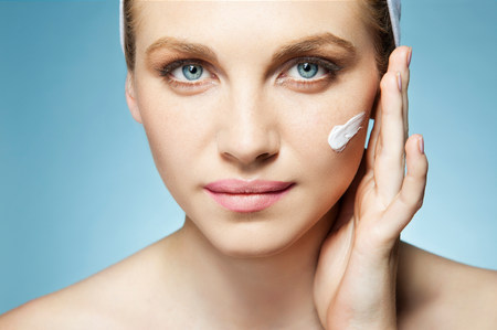 Woman applying moisturiser LANG_EVOIMAGES
