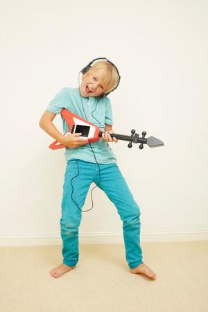 Boy wearing headphones playing guitar LANG_EVOIMAGES