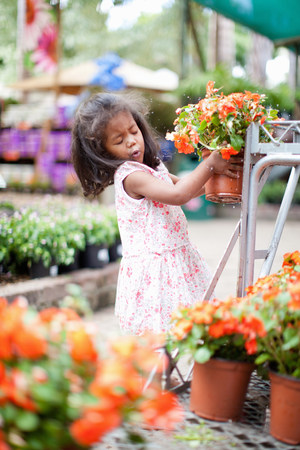 Girl holding potted plant in nursery LANG_EVOIMAGES
